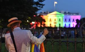"""2015年6月26日,美国华盛顿,一位同性婚姻支持者手持彩虹旗,站在变成了象征着""""同性恋骄傲""""的彩虹色的美国白宫外。"""