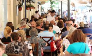 希腊公投后,一些人排队领救济食品,一些人吃大餐