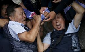 """当地时间2015年8月24日,韩国坡州,在通往非军事化区域的统一桥附近的检查站,抗议者与警察争抢一面朝鲜国旗。据韩联社报道,韩朝高级别对话经过为期四天的""""马拉松谈判"""",于25日凌晨达成协议。"""