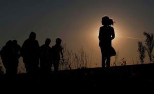 当地时间2015年9月12日,匈牙利,难民在日落时分沿着靠近勒斯凯的难民收容点的铁轨步行。