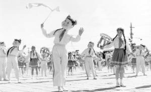 1958年的国庆节,首都少先队员们在天安门前跳大头娃娃舞。 新华社 图