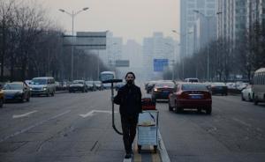 """2015年11月29日,北京,一位来自深圳、自称""""坚果兄弟""""的小伙,完成了他使用工业吸尘器为北京吸雾霾100天的《尘埃计划》第一部分。次日,他携带这些灰尘赶赴唐山一家制砖厂,将用灰尘做一块板砖。北京吸霾第98天,""""坚果兄弟""""在望京SOHO建筑群周边作业。 视觉中国"""