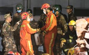 搜救人员在一处有疑似生命体征信号的坍塌处搜寻,救援人员在传递生命探测设备。 澎湃新闻记者 赵昀 图