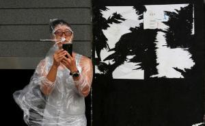"""10月21日,香港,一名男子在强风中看手机。当日清晨,香港天文台发出八号烈风或暴风信号,台风""""海马""""集结在香港东南偏东。""""海马""""是今年以来袭击香港的最强风暴之一,有部分居民不甘宅家中,玩出新高度,有迎着风玩大鹏展翅的,有不怕手机进水迎着风雨玩自拍的,还有拖家带口去海边看浪的…… 视觉中国 图"""