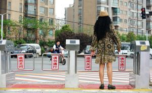 """4月19日,湖北武汉,金银潭大道一处红绿灯路口,新安装的两排六道口闸机已经启用。在与周边护栏连成一体后,闸机将被用来防止""""中国式过马路""""。这些闸机由系统自动控制,红灯关绿灯开。闸机旁设有红色禁止站立区,以及黄线外的行人等待区,闸机后方还设有一个监控大屏幕和两个摄像头,行人如果闯红灯过马路将会被抓拍,并同步显示在屏幕上。   视觉中国 图"""