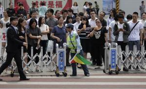"""2017年6月2日报道,近日,北京王府井大街南口的人行横道线旁在已经拥有了交通协管员的基础上,再安装了人行道闸机通道,协管员在红灯时将闸机关闭,绿灯时打开,提醒行人遵守交通规则,提高道路通行效率。这款整治""""中国式过马路""""的神器引起了人们的极大关注。东方IC 图"""