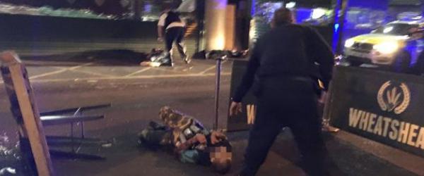 博罗市场,警察在两名嫌疑犯旁,嫌犯被击中后倒地。视觉中国 图