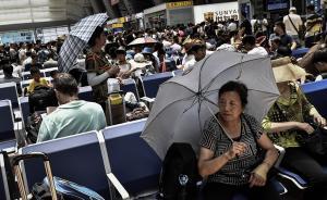 7月12日中午时分,北京南站候车大厅里,由于部分区域受阳光直射,为躲避阳光,许多旅客撑伞候车。据北京市气象台消息,7月12日正式入伏,北京今日最高气温达36℃。图为旅客撑伞躲避阳光直晒。本图集均为东方IC