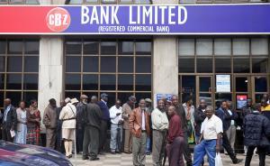 当地时间2017年11月15日,在津巴布韦首都哈拉雷,人们在银行外排队取钱。